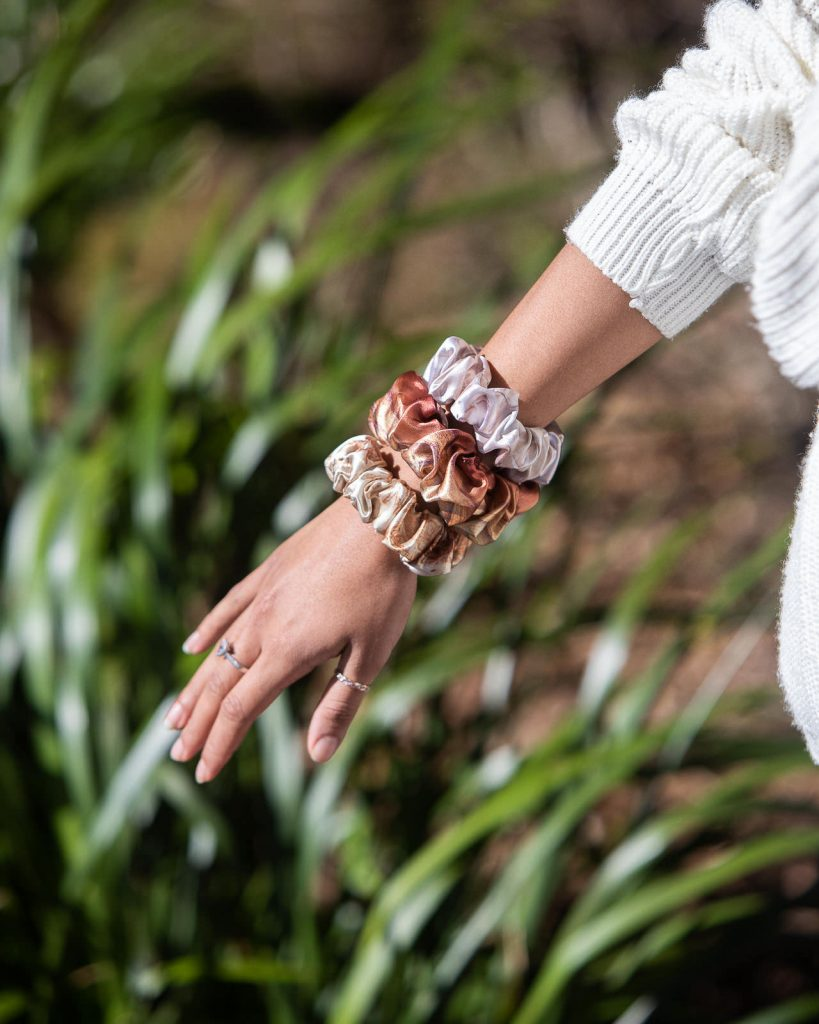 Brown and white satin scrunchies close up photo worn on wrist of young model