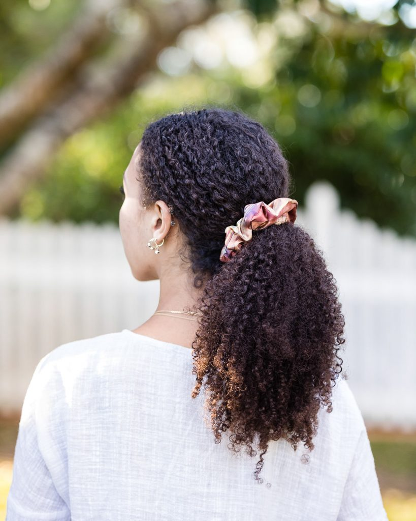 Satin scrunchie hair accessory worn by young model with curly hair at a fashion photoshoot