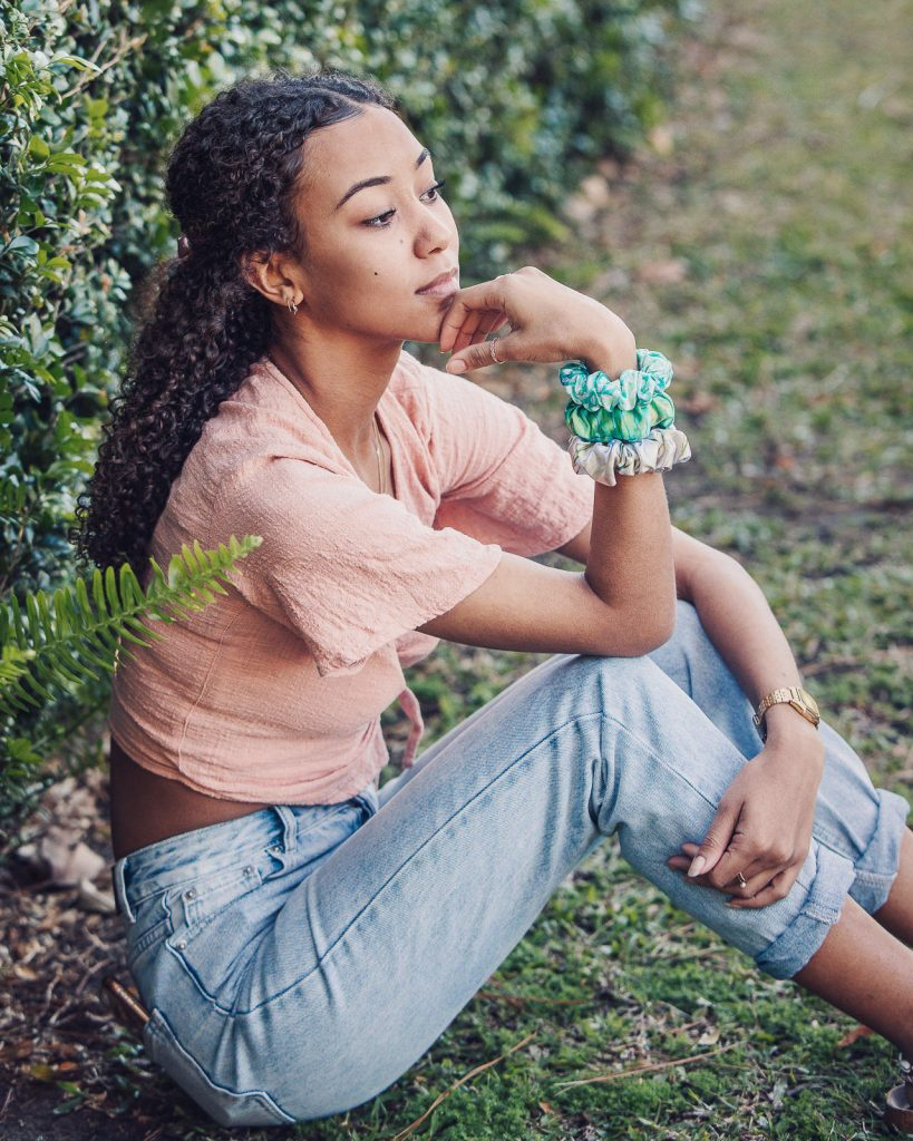 A young model at a photoshoot for wears satin scrunchies on her wrist as she poses on the grass