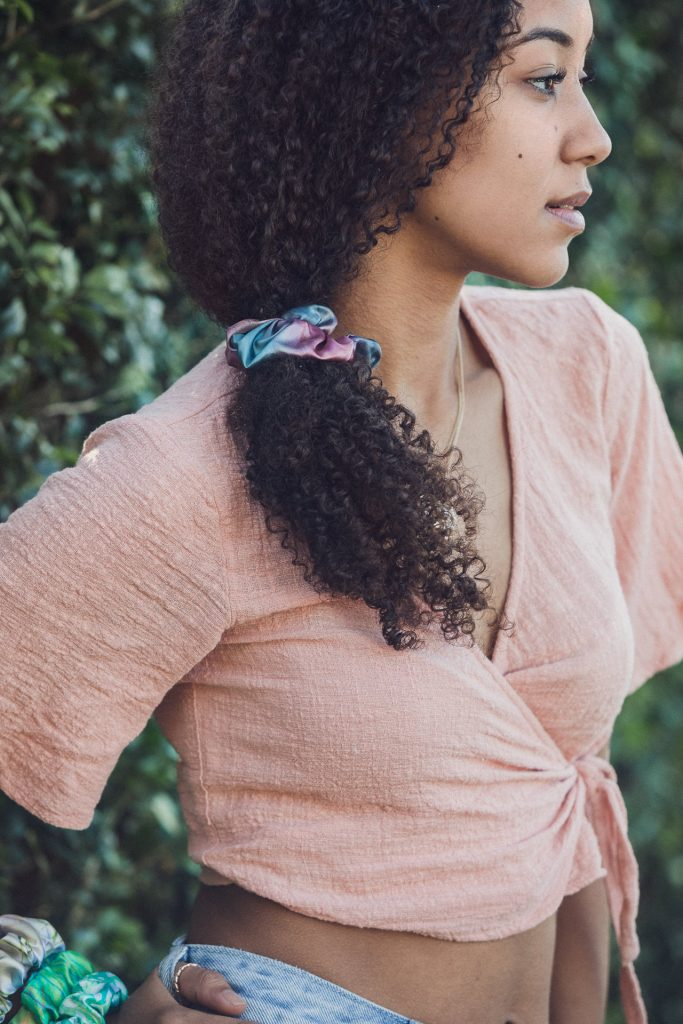 A blue sage green and magenta satin scrunchie hair accessory in the curly hair of a young model at a commercial photo shoot