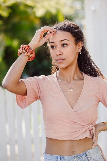 A beautiful young girl with a satin scrunchie on her wrist models for a commercial fashion photo shoot